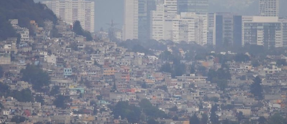 Buildings and houses stand shrouded in smog in Mexico City, March 16, 2016. Mexico City's government ordered traffic restrictions and recommended people stay indoors due to serious air pollution, issuing its second-highest alert warning for ozone levels for the first time in 13 years.
