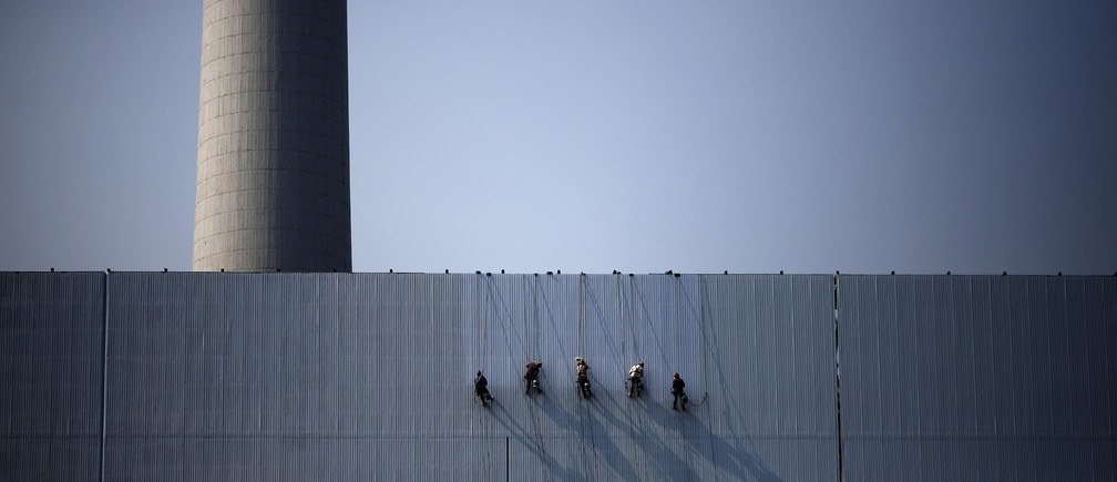 Workers paint an exterior wall of a power plant in Beijing, July 15, 2014. China's leaders are expecting to see a dividend from three months of stimulus spending in second-quarter growth data on July 16, 2014, but the economy may need even more state support to meet this year's growth target of 7.5 percent. Picture taken July 15, 2014. REUTERS/Kim Kyung-Hoon (CHINA - Tags: BUSINESS ENERGY POLITICS EMPLOYMENT TPX IMAGES OF THE DAY) - GM1EA7G00Y101