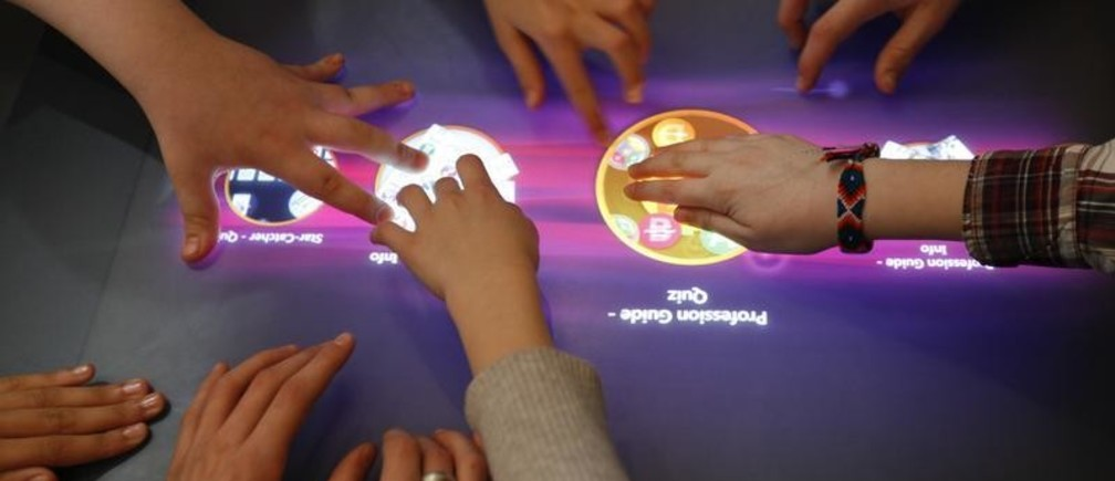 Pupils of Berlin's Hausburg European school use a Microsoft Surface multi-touch computer in a digital classroom at the Microsoft stand during a presentation at the CeBIT exhibition centre in Hanover March 1, 2010. The new Microsoft Surface does not require a keyboard and mouse to operate, providing users with a new way of dealing with digital content. The world's largest IT fair CeBIT opens its doors on March 2 and runs through March 6.       REUTERS/Fabrizio Bensch (GERMANY - Tags: SCI TECH BUSINESS) - BM2E63117TS01