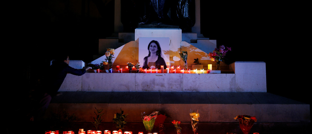 An activist places candles and flowers on the Great Siege monument, after rebuilding a makeshift memorial to assassinated anti-corruption journalist Daphne Caruana Galizia, during a vigil and protest to mark thirteen months since her murder, in Valletta, Malta November 16, 2018.  REUTERS/Darrin Zammit Lupi - RC15B01C47A0