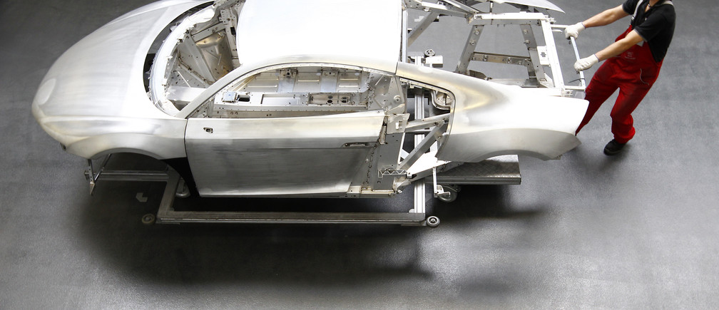 A worker moves a new Audi R8 car body in the automotive welding and assembly lines hall of the German car manufacturer's plant in Neckarsulm July 3, 2013.   REUTERS/Michaela Rehle (GERMANY - Tags: TRANSPORT BUSINESS) - BM2E97516CC01