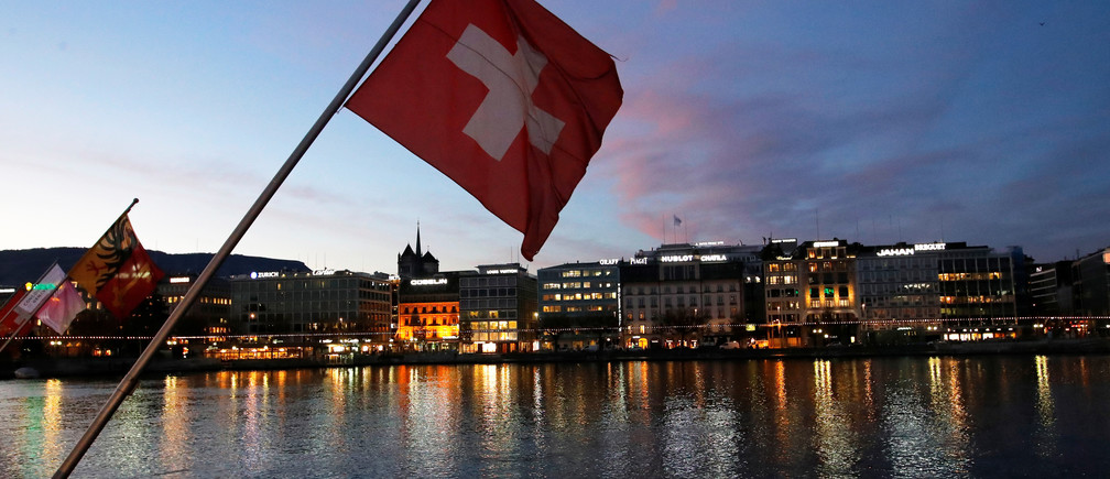 A Swiss flag is pictured during the sunrise on the Commercial and Financial District in Geneva, Switzerland, November 23, 2017. REUTERS/Denis Balibouse - RC13334AABF0