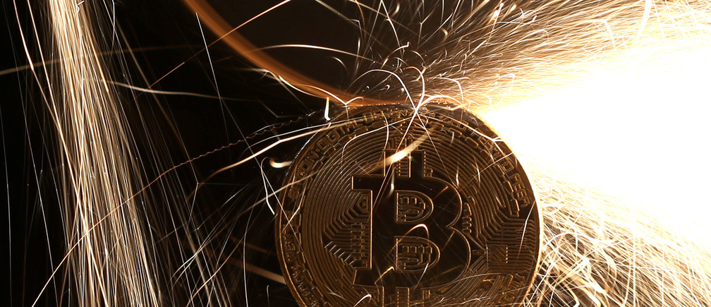 Sparks glow from broken Bitcoin (virtual currency) coins.