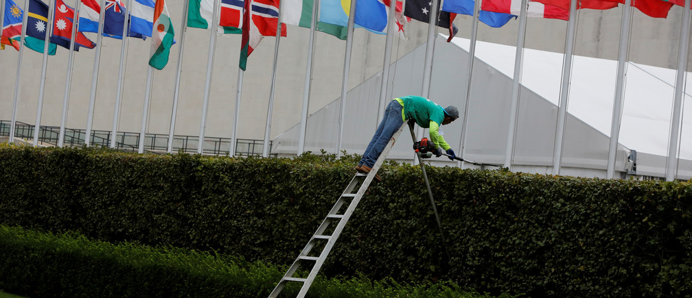 A worker trims hedges outside the United Nations Headquarters in New York City, U.S., August 29, 2017  REUTERS/Andrew Kelly - RC15F3B5B210