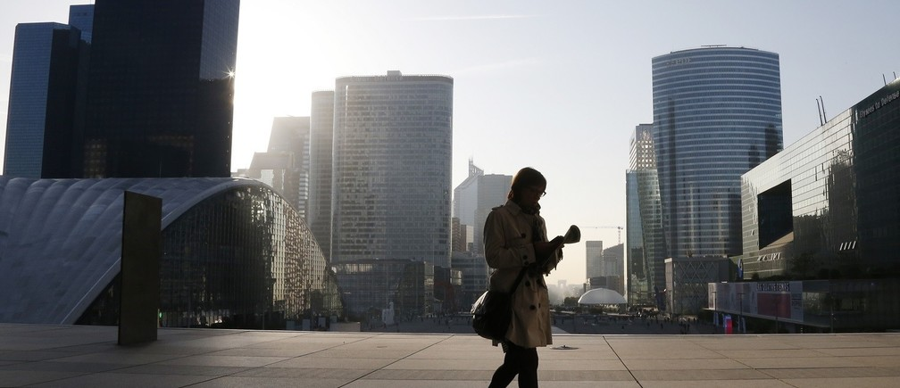 A woman walks on the esplanade of La Defense, in the financial and business district in La Defense, west of Paris, April 10, 2014.