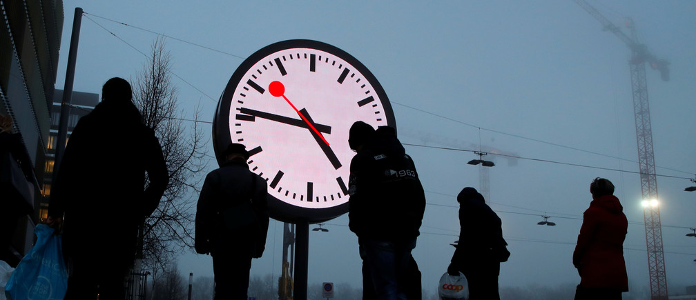 Commuters wait for the bus next to a giant Mondaine electronic station clock near the Swiss railway company SBB building in Bern, Switzerland December 7, 2017. REUTERS/Denis Balibouse - RC16468D3190