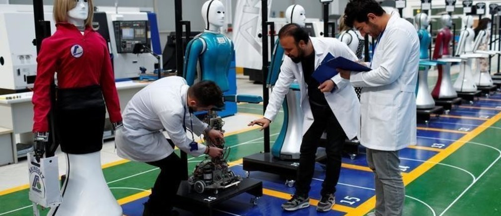 """Ozgur Akin, Chairman and founder of Akinsoft, and engineers check an """"ADA G4"""" humanoid robot at Akinrobotics, the country's first-ever factory to mass produce humanoid robots, in Konya, Turkey, December 8, 2017. Picture taken December 8, 2017. REUTERS/Murad Sezer - RC1AFEDC7560"""