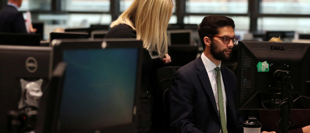 Employees work at a desk in the Lloyd's of London building in the City of London financial district in London, Britain, April 16, 2019. Picture taken April 16, 2019. REUTERS/Hannah McKay - RC1708B123A0