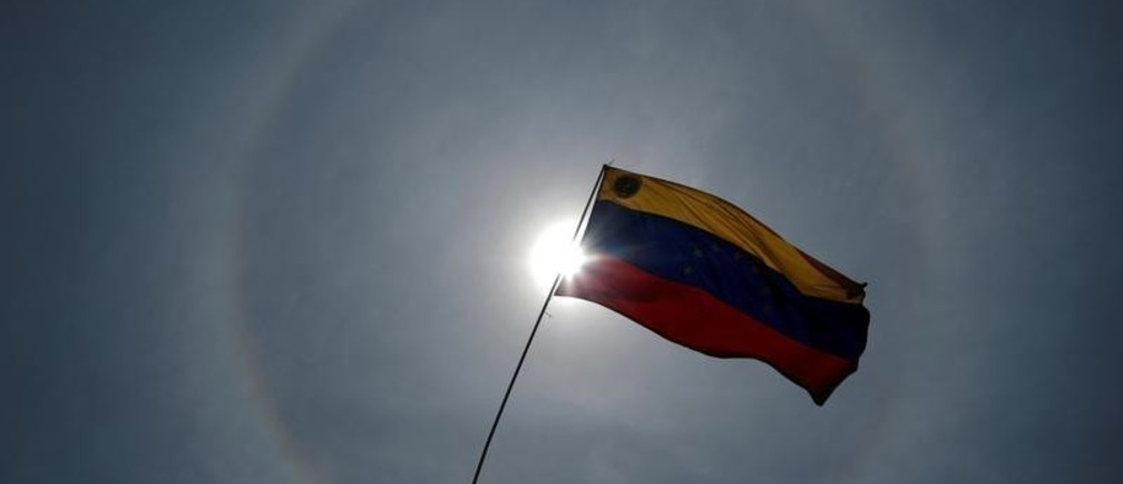 An opposition supporter holds a Venezuelan flag during arally against the government of Venezuela's President Nicolas Maduro and to commemorate May Day in Caracas Venezuela, May 1, 2019. REUTERS/Ueslei Marcelino - RC1FCEF66C20