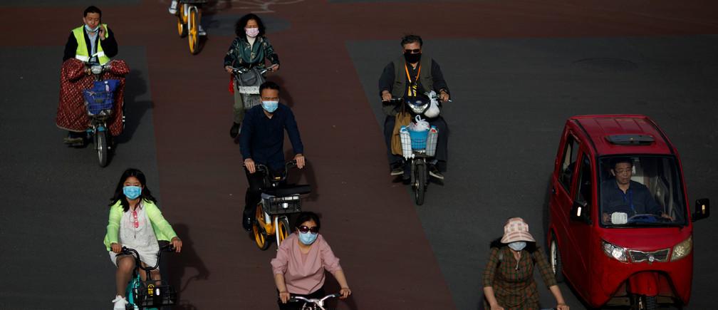 La gente usa protección durante la hora punta de la tarde después de la propagación de la nueva enfermedad coronavirus (COVID-19) en Beijing, China, el 12 de mayo de 2020.