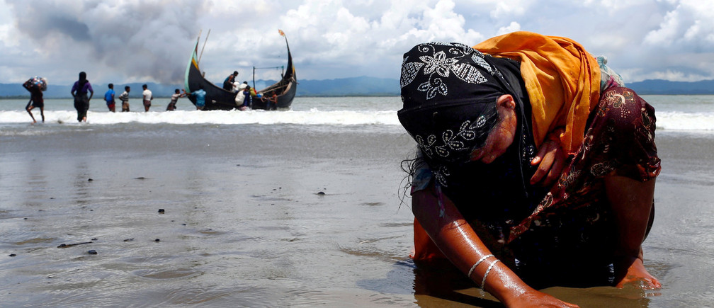 "An exhausted Rohingya refugee woman touches the shore after crossing the Bangladesh-Myanmar border by boat through the Bay of Bengal, in Shah Porir Dwip, Bangladesh September 11, 2017. Reuters photographer Danish Siddiqui: ""It was a clear morning and I could see the several clouds of smoke in the background on the Myanmar side. After a few hours waiting on the beach the fishing boats started arriving with Rohingyas. This image was taken just after a family member of the Rohingya woman carried her from the boat. The exhausted Rohingya woman sat on the beach and put her hand to feel the shore after the long and dangerous journey from Myanmar."" REUTERS/Danish Siddiqui/File Photo  SEARCH ""POY ROHINGYA"" FOR THIS STORY. SEARCH ""REUTERS POY"" FOR ALL BEST OF 2017 PACKAGES.  TPX IMAGES OF THE DAY. - RC1FA77239A0"