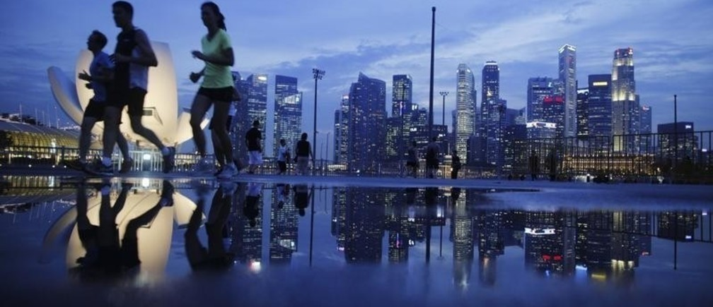Joggers run past as the skyline of Singapore's financial district is seen in the background April 21, 2014. REUTERS/Edgar Su (SINGAPORE - Tags: CITYSCAPE SPORT ATHLETICS BUSINESS SOCIETY) - RTR3M2JB
