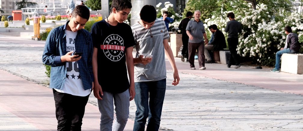 Iranian youth use their mobile phones as they walk at a park in Tehran, Iran, May 16, 2017. REUTERS/TIMA ATTENTION EDITORS - THIS IMAGE WAS PROVIDED BY A THIRD PARTY. FOR EDITORIAL USE ONLY. - RTX3636P