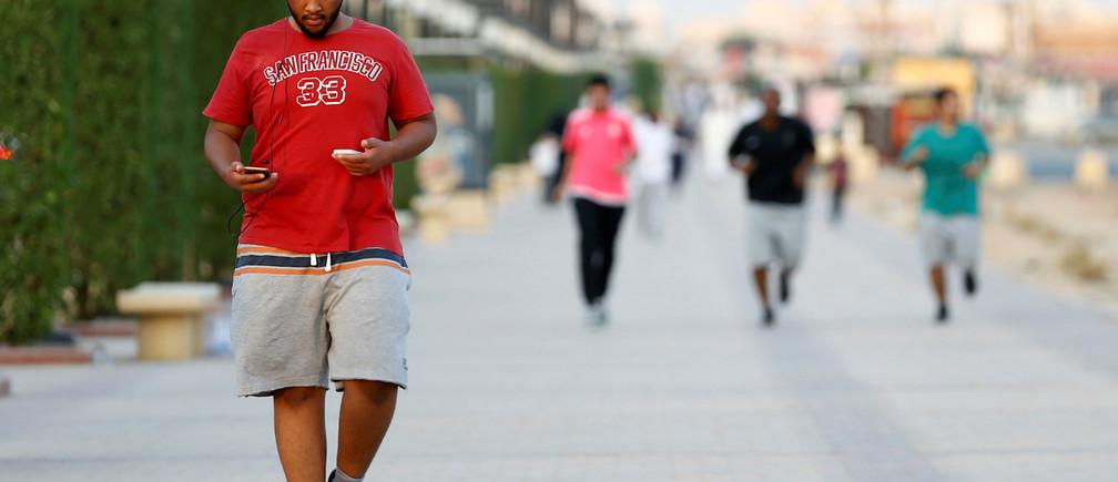 A Saudi man uses his smartphone as he walks on a sidewalk in Riyadh, Saudi Arabia September 21, 2017.   REUTERS/Faisal Al Nasser - RC16B5879800