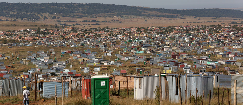 A man walks past a public toilet at Lawley informal settlement in the south of Johannesburg, South Africa, May 2, 2019. Picture taken May 2, 2019. REUTERS/Siphiwe Sibeko - RC11E91AD260