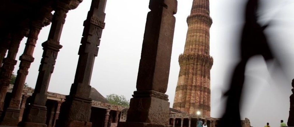 A tourist walks past the illuminated 72.55 (238 ft) meter high Qutab Minar in New Delhi May 17, 2005. Authorities last week improved lighting of the 13th century monument and opened it at night to attract tourists. The monument tapers from a 15-meters (49.2 ft) diameter base to just 21/2 meters (8.2 ft) at the top. REUTERS/Kamal Kishore  KK/JJ - RP6DRMRNMMAD