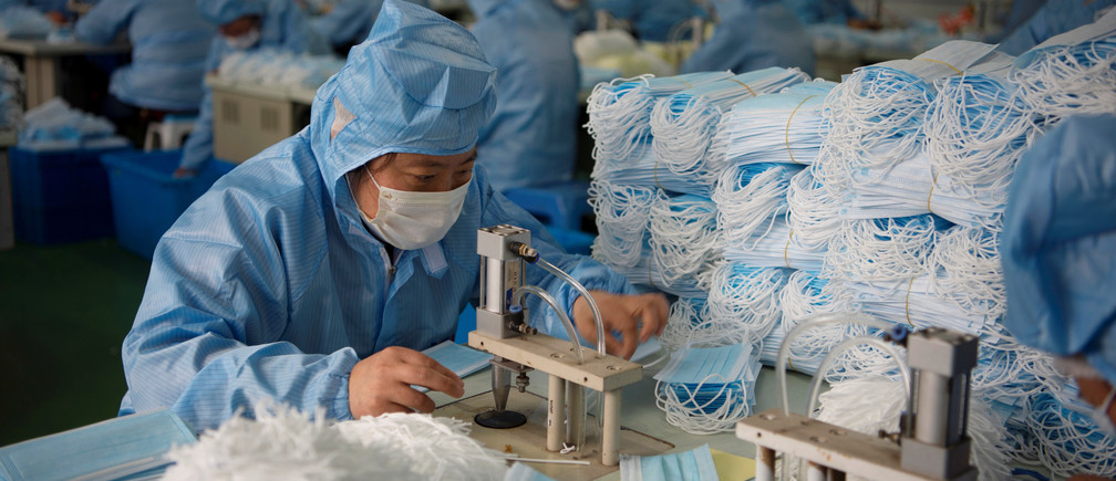 Employees work on a production line for surgical masks at a factory, following an outbreak of the novel coronavirus in the country, in Nantong, Jiangsu province, China February 14, 2020. China Daily via REUTERS  ATTENTION EDITORS - THIS IMAGE WAS PROVIDED BY A THIRD PARTY. CHINA OUT. - RC290F9NRWZG