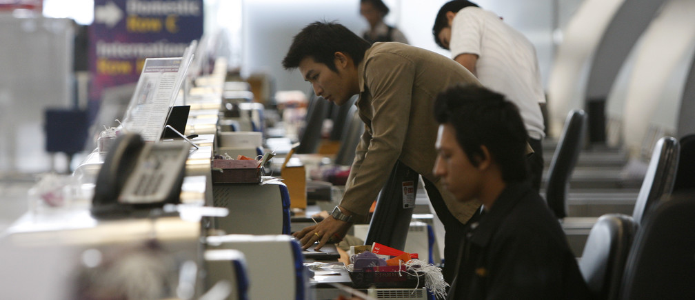 Airport workers start up computers at the check-in counter as anti-government protesters pack up to leave Bangkok's Suvarnabhumi International Airport December 3, 2008.