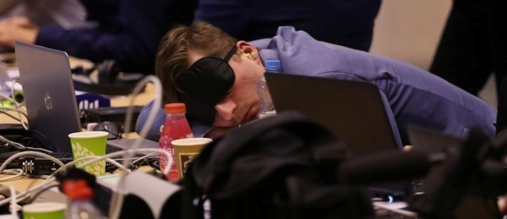 A journalist sleeps while waiting for the end of a European Union leaders summit that aims to select candidates for top EU institution jobs, in Brussels, Belgium July 1, 2019. REUTERS/Yves Herman - RC1563E23B50