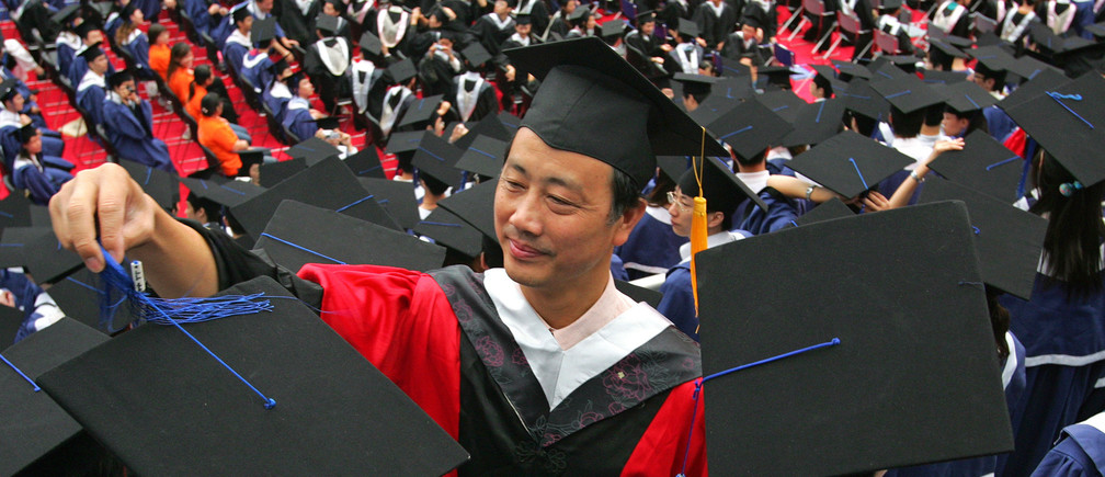 A man adjusts a student's mortar board during the graduation ceremony at Fudan University in Shanghai June 28, 2006. With about 750,000 more students graduating into the workforce this year compared to last, the competition is getting tougher, leaving the 20-somethings whose studies have often left them with little practical know-how floundering to find work. Picture taken June 28, 2006.  TO MATCH FEATURE CHINA GRADUATES      REUTERS/Aly Song (CHINA) - GM1DSYEPDMAA