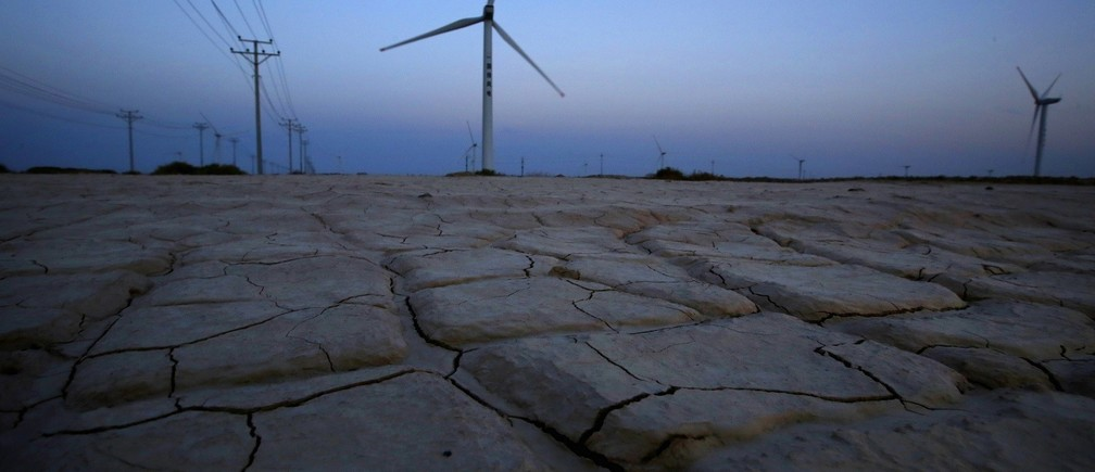 """Cracked earth marks a dried-up area near a wind turbine used to generate electricity at a wind farm in Guazhou, 950km (590 miles) northwest of Lanzhou, Gansu Province September 15, 2013. China will be """"flexible"""" in U.N. talks for a new global climate change deal, but the key to progress is getting rich nations to keep pledges to fund mitigation steps by poorer countries, the country's top climate change official said on November 5, 2013. Picture taken September 15, 2013."""