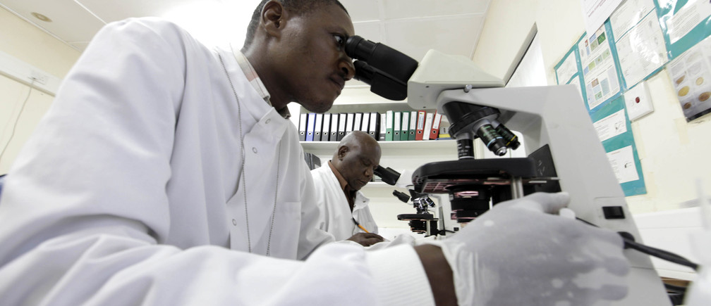 Kenya Medical Research Institute doctors research malaria at the clinical research facility laboratory in the Kenya coastal town of Kilifi, November 23, 2010. Malaria threatens half the people on the planet and kills around 800,000 people a year, many of them too young to have even learned to walk. The death rate has come down in the last decade, but full-scale eradication will cost billions and drag funds away from other equally, or possibly even more urgent health efforts. As governments in poor countries and donors from wealthy ones weigh up where to put their money, experts have begun a quiet but fundamental debate about whether wiping out malaria is realistic or even makes economic sense.Picture taken November 23, 2010.   To match Special Report MALARIA/COST     REUTERS/Joseph Okanga (KENYA - Tags: BUSINESS HEALTH) - RTXVPM1