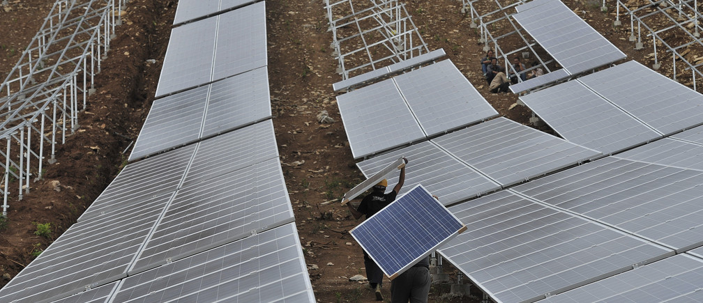 Workers carry solar panels at a solar power plant in Anhui province, China