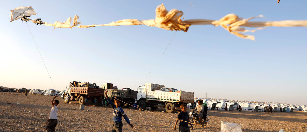 Children fly their kites as they play inside a refugee camp for people displaced by fightings between the Syrian Democratic Forces and Islamic State militants in Ain Issa, Syria October 3, 2017.         REUTERS/Erik De Castro - RC1C3D183EB0
