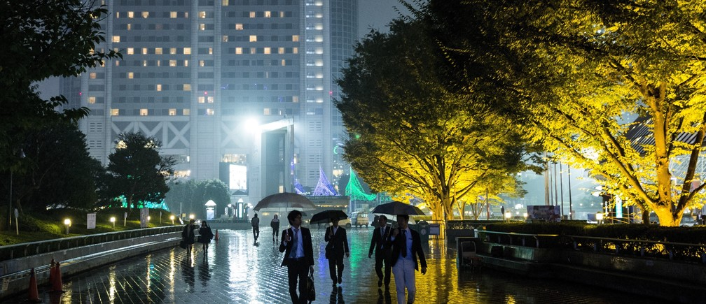 People walk past illuminated trees on a rainy night in Tokyo October 16, 2015.