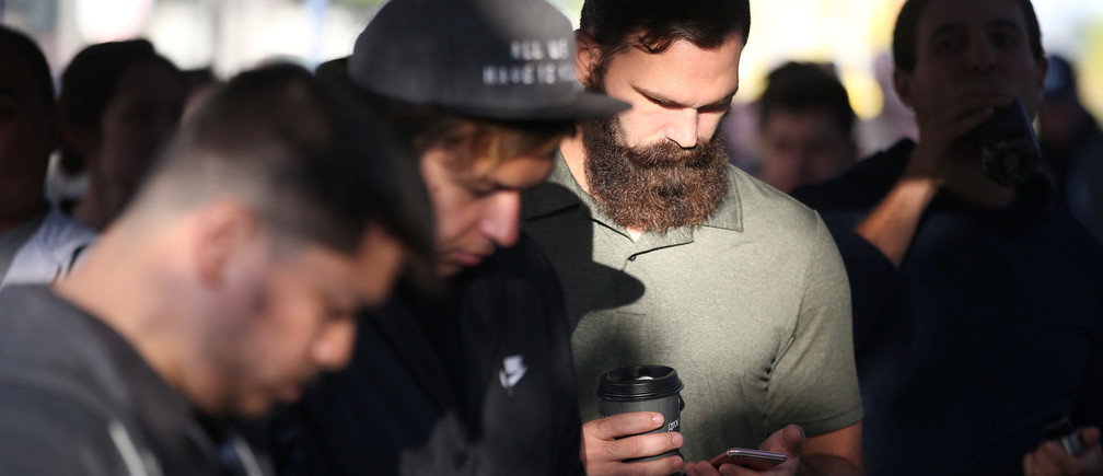People browse their phones as they wait in line to buy the new iPhone 7 smartphone outside an Apple Inc. store in Los Angeles, California, U.S., September 16, 2016. REUTERS/Lucy Nicholson - RTSO2RT