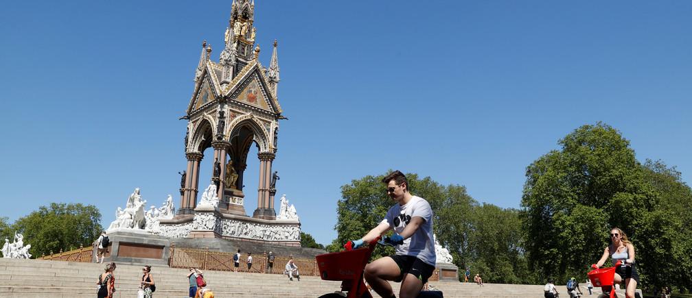 La gente pasa en bicicleta por el Albert Memorial en Kensington Gardens, tras el brote de la enfermedad coronavirus (COVID-19), Londres, Gran Bretaña, 30 de mayo de 2020.