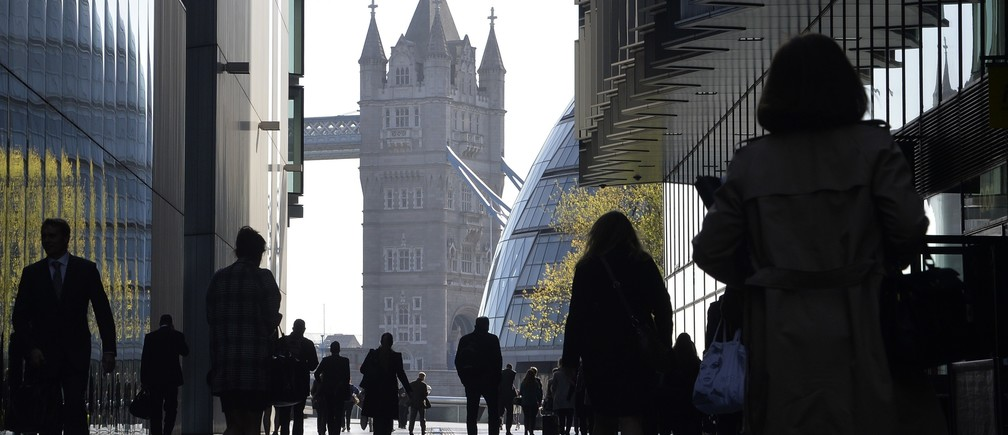 City workers head to work during the morning rush hour in Southwark in central London April 16, 2014.