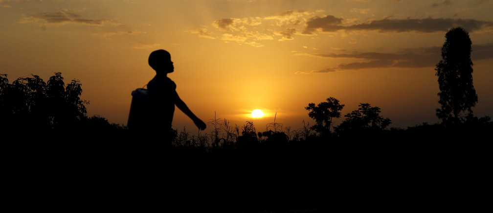 A boy carries a bucket at sunset in the village of Kogelo, west of Kenya's capital Nairobi, July 15, 2015.