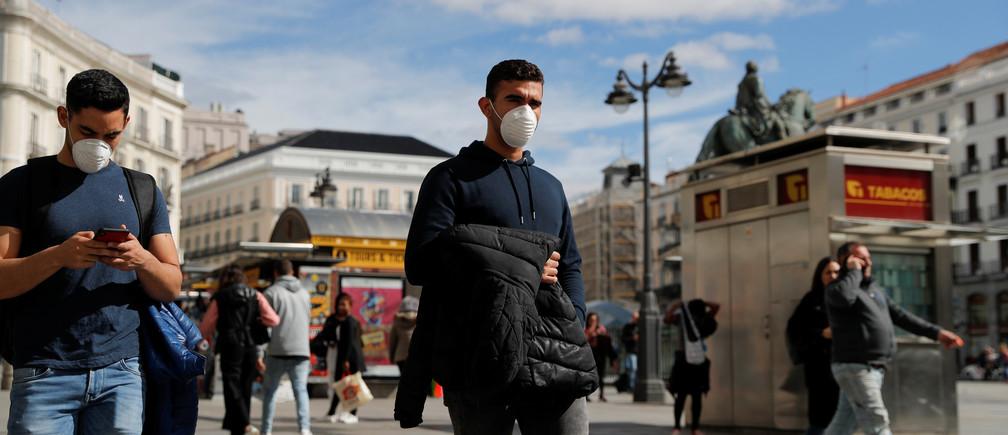 Hombres llevan máscaras protectoras cuando caminan por la plaza de la Puerta del Sol en Madrid, España, el 4 de marzo de 2020.