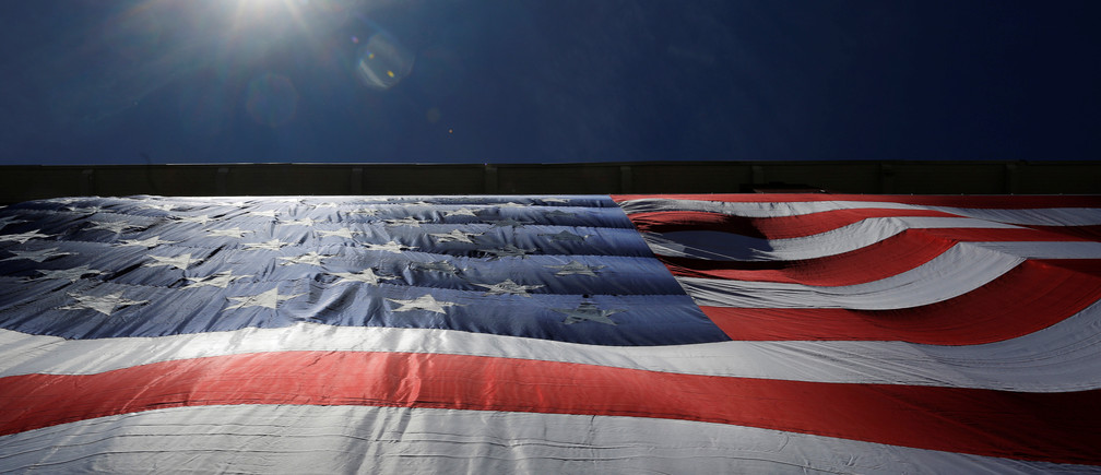 """As 95-by-50-foot American flag is unfurled on the side of an apartment complex, a replica of the """"The Great Flag"""" that was spun, woven, dyed, constructed and displayed on the same building by Amoskeag Manufacturing Company in 1914, in Manchester, New Hampshire, U.S., June 14, 2017.   REUTERS/Brian Snyder - RTS173F7"""
