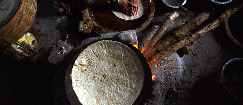An Indian fisherwoman prepares a meal on a wood-burning stove in her home near Mumbai