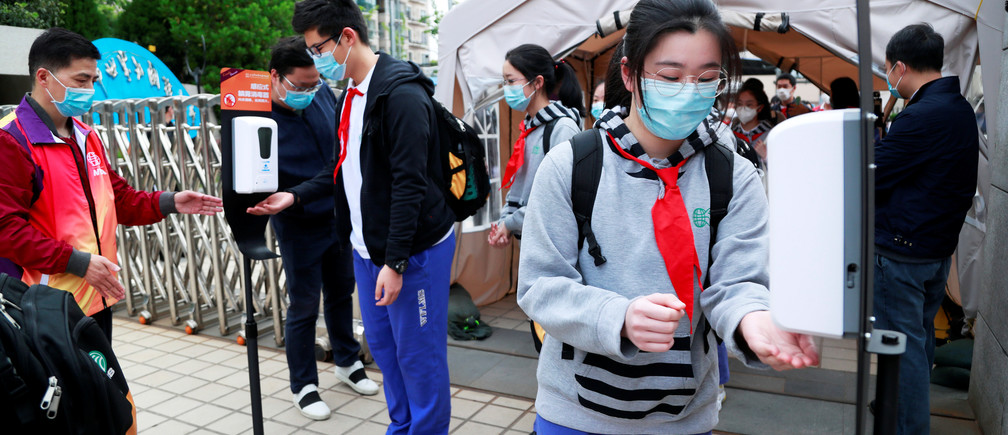 Students wearing face masks use hand sanitisers at an entrance to a school in Shanghai, China, as senior high school and senior middle school students in Shanghai return to campus following the coronavirus disease (COVID-19) outbreak, April 27, 2020. cnsphoto via REUTERS   ATTENTION EDITORS - THIS IMAGE WAS PROVIDED BY A THIRD PARTY. CHINA OUT. - RC2SCG9A3Y1I