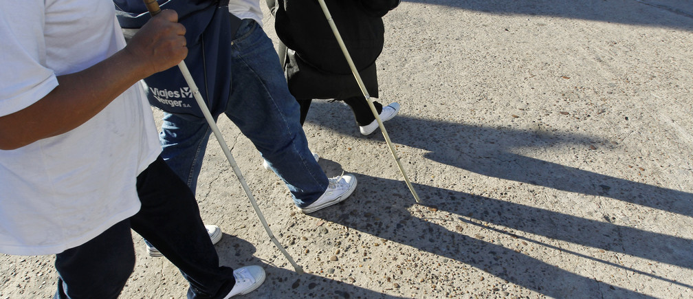 """Eusebia Casimiro (L), who was left blind as an adult during surgery to remove a brain tumour, and her husband Leonardo Duarte (C), also blind, walk to a bus as they travel to perform in a Carnival street theatre called """"murga"""", in Buenos Aires, April 20, 2013. Leonardo and Eusebia are two of around 400,000 blind people in Argentina, who despite having their lives improved through the legalization of guide dogs in more public places, still face a lack of jobs, a major problem according to the Association for Aid to the Blind. Picture taken April 20, 2013.     REUTERS/Enrique Marcarian (ARGENTINA - Tags: SOCIETY HEALTH) - GM1E9AM00GX01"""