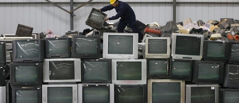 An employee arranges discarded televisions at a newly opened electronic waste recycling factory in Wuhan, Hubei province March 29, 2011. According to the U.S. Environmental Protection Agency (EPA), e-waste is the fastest growing commodity in the waste stream, with a growth rate five times that of other parts of the business such as industrial waste. The burgeoning middle classes in fast-growth China and India mean there are more computers and mobiles, adding to e-cycling growth. REUTERS/Stringer (CHINA - Tags: ENVIRONMENT BUSINESS SCI TECH IMAGES OF THE DAY) CHINA OUT. NO COMMERCIAL OR EDITORIAL SALES IN CHINA - GM1E73T1GZH01