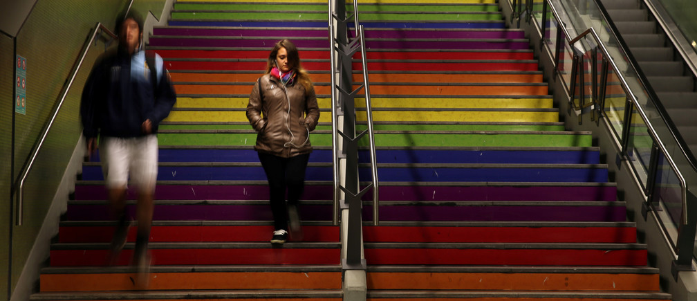 A woman and a man walk down the stairs painted in the colors of the rainbow at a subway station to celebrate International Day Against Homophobia in Buenos Aires, Argentina, May 17, 2017. REUTERS/Marcos Brindicci - RC1C1F074710