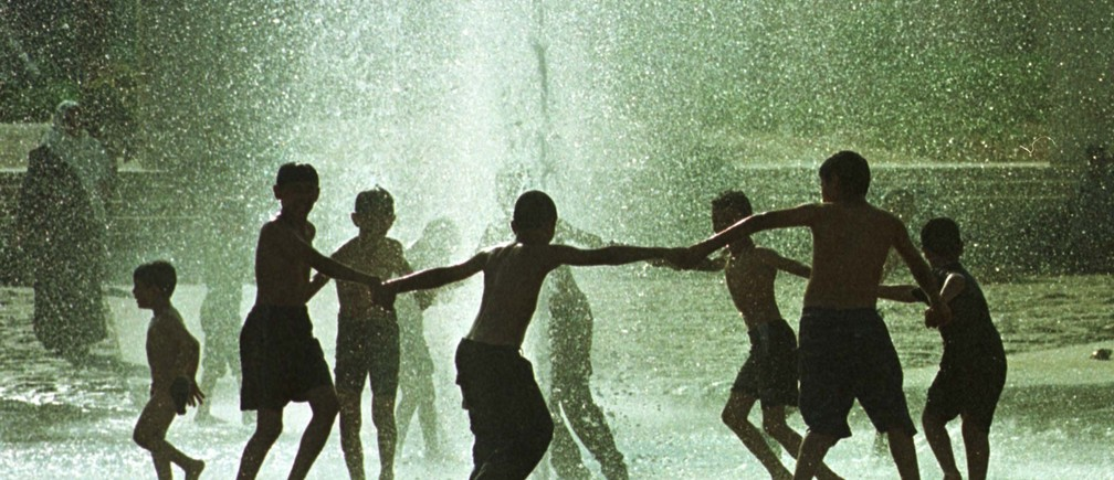 Young Jordanians splash and play in a public fountain in the centre of Amman July 29,2000 as hundreds of local citizens rushed to cool down in public swimming pools as a heat wave struck the kingdom where temperatures reached 42 degrees Celsius, at least 9 nine degrees above the national average for the time of the year.