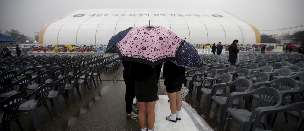Students holding umbrellas visit the official memorial altar for the victims of the ferry disaster that killed more than 300 passengers on the occasion of the first anniversary, in Ansan April 16, 2015.  REUTERS/Kim Hong-Ji - GF10000060875