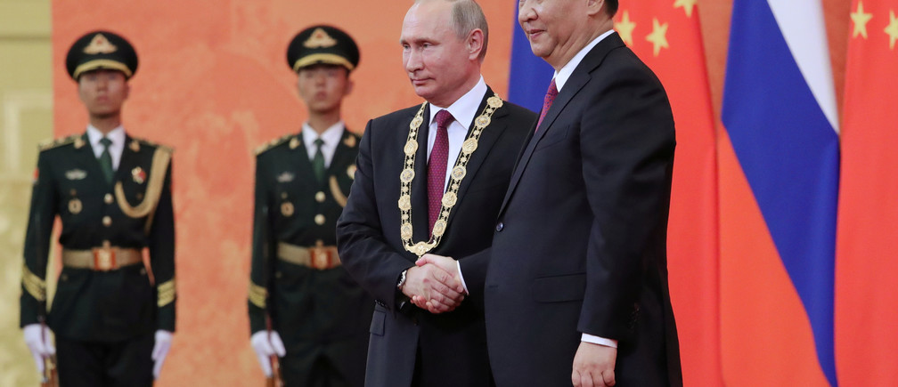 Chinese President Xi Jinping (R) shakes hands with Russian President Vladimir Putin after presenting him with the Friendship Medal during a ceremony in the Great Hall of the People in Beijing, China June 8, 2018. Sputnik/Mikhail Klimentyev/Kremlin via REUTERS  ATTENTION EDITORS - THIS IMAGE WAS PROVIDED BY A THIRD PARTY. - RC11DC16F780