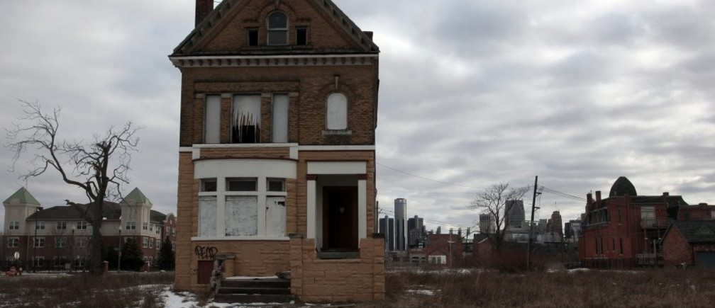 A vacant, boarded up house is seen in the once thriving Brush Park neighborhood with the downtown Detroit skyline behind it in Detroit, Michigan March 3, 2013. Michigan Governor Rick Snyder cleared the way for a state takeover of Detroit, declaring that the birthplace of the U.S. automotive industry faces a fiscal emergency and that he has identified a top candidate to assume its management. Friday's declaration by the Republican governor virtually assures that the state of Michigan will assume control of Detroit's books, and eventually decide whether the city should file the largest municipal bankruptcy in U.S. history.