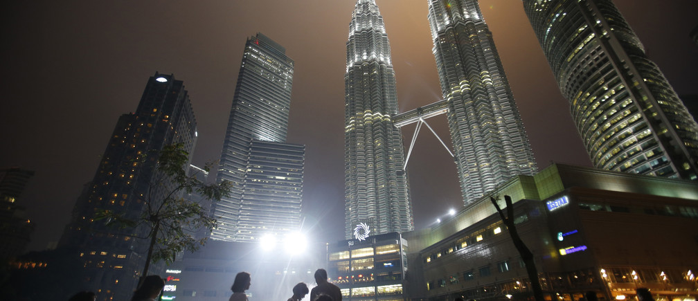 Tourists gather near the foot of the haze-covered landmark Petronas Twin Towers in Kuala Lumpur June 25, 2013.