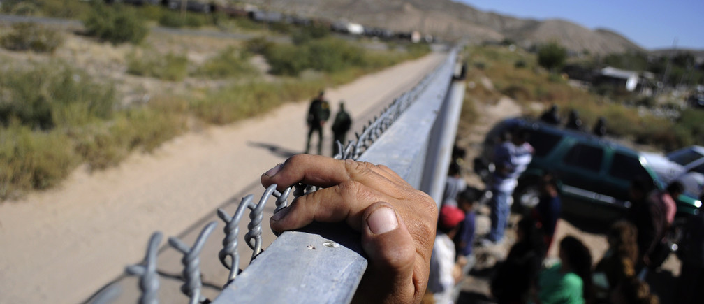 A person holds onto the fence marking the border between the United States and Mexico in Ciudad Juarez November 2, 2010.