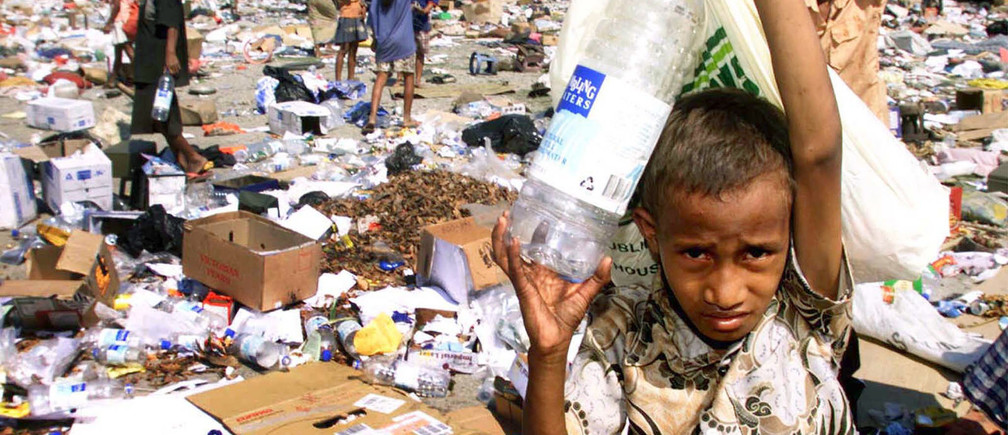 East Timorese collect plastic containers and leftovers at a garbage dump in Dili September 27.  Indonesia's armed forces handed military control of East Timor to U.N. troops on Monday, formally marking Indonesia's first big step out of the territory it has ruled for almost 24 years.