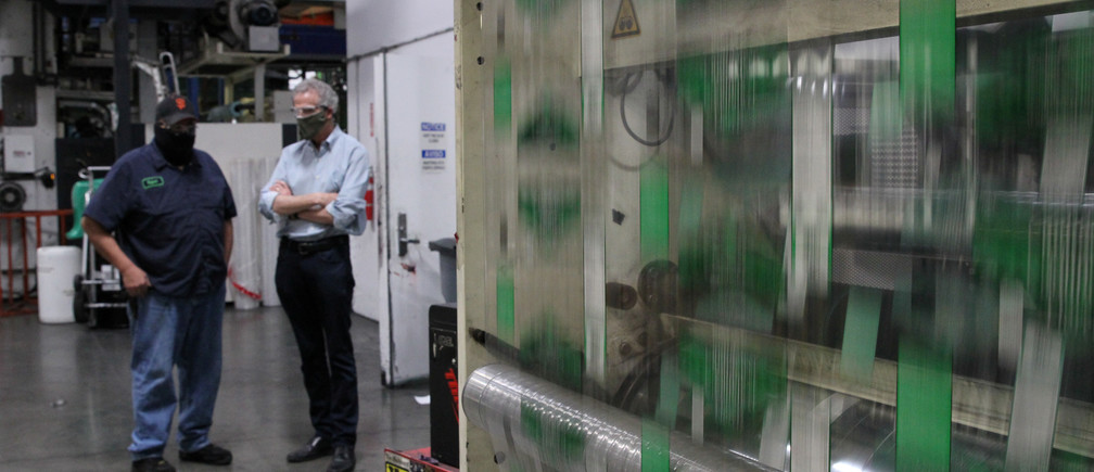 Kevin Kelly, CEO of Emerald Packaging, talks with an employee as they wear protective masks on a production floor of the company, which prints packaging material to be used for produce, amid the coronavirus disease (COVID-19) outbreak, in Union City, California, U.S. on May 7, 2020. Picture taken May 7, 2020. REUTERS/Nathan Frandino - RC21PG9H6SW7
