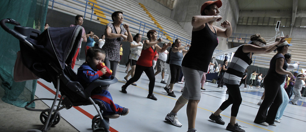 A child waits in his pram while his mother participates in an aerobics class at the gymnasium of a sports center in Cartago, east of San Jose July 10, 2012. More than 300 people participate in aerobics program organized by a local committee, with the objective of reducing heart disease, obesity and sedentary lifestyle of the population of Cartago, according to program director Ivonne Martinez. REUTERS/Juan Carlos Ulate (COSTA RICA - Tags: HEALTH SOCIETY) - RTR34T2M
