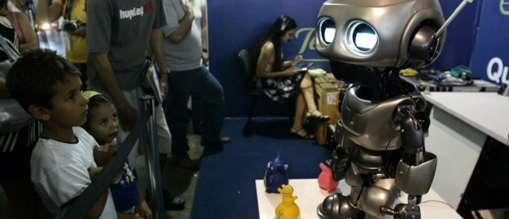 """Children interact with a robot during the annual """"Campus Party"""" Internet users gathering in Sao Paulo February 13, 2008."""